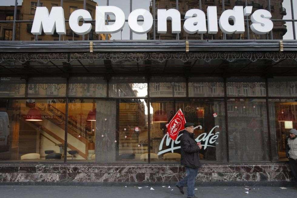 Un piquete informativo pasa frente a un restaurante de comida rápida en Gran Vía.